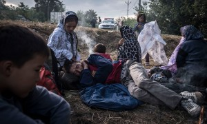 Refugees warm near the fire as they wait for escort being detained by Hungarian police after crossing the Serbia-Hungaria birder outside Asotthalom, Hungary, Sunday August, 23, 2015. (Photo Sergey Ponomarev for The New York Times) NYTCREDIT: Sergey Ponomarev for The New York Times