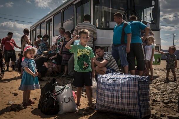 Refugees wait to board a bus to the the train station where they will be taken for constant living in Russia from the refugee camp at Donetsk, Russia, Thursday August 21, 2014. (Photo Sergey Ponomarev for The New York Times) NYTCREDIT: